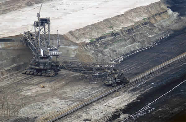 Vast crane extractor dwarfs huge trucks in open cast brown coal mine