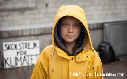 Climate 2020 | Photo portrait of Greta Thunberg in yellow sou'wester, hood up looking directly at you - credit Anders Helberg | Effeckt